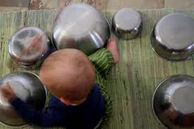 Photograph of child playing with pots and pans