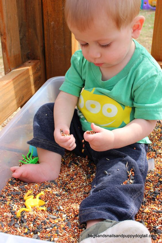 boy playing with seeds in an outdoor tray