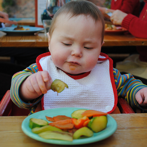 baby in high cahir eating fruit slices from a small plate